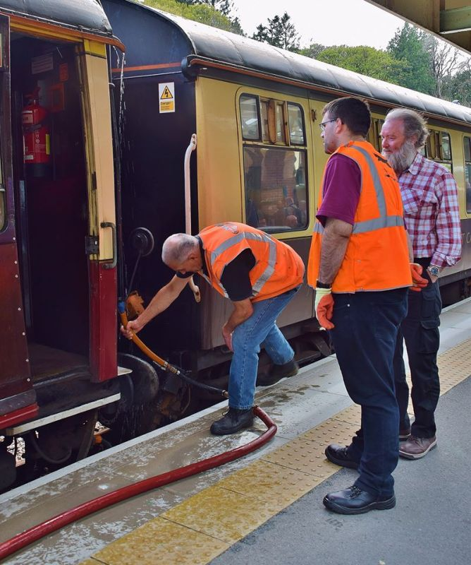 Geoff Brookes watering one of the railtour coaches, and doubtless getting some welcome advice from his audience.